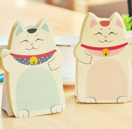 sticky notes pad shaped like the Asian Lucky Cat symbol. Each pad is a pastel colour on cream or white. The pads will stand up on a paper/cardboard base which is part of the pad. Depending on the colour of the pad the cat is either waving its right paw or left paw.